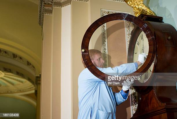 S Senate museum specialist Richard Doerner moves the arms of the Ohio Clock to the correct time before winding the historic timepiece in the Capitol...