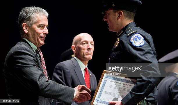 Senate Sergeant at Arms Frank Larkin left shakes hands with a newly swornin US Capitol Police officer from Recruit Officer Class during the US...