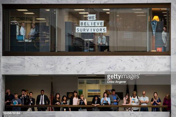 Senate staffers look on as protesters rally against Supreme Court nominee Judge Brett Kavanaugh in the atrium of the Hart Senate Office Building on...