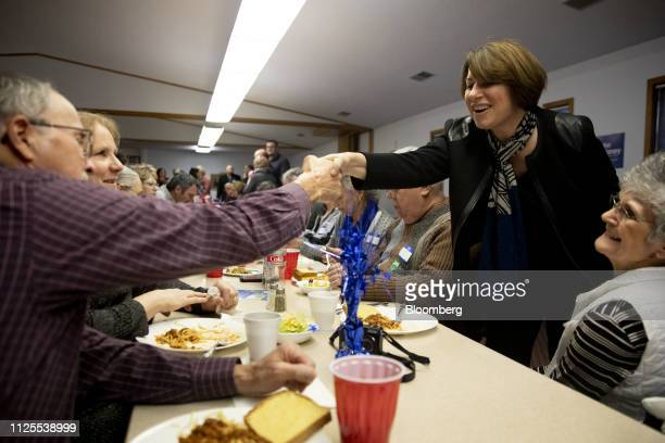 Senator Amy Klobuchar a Democrat from Minnesota and 2020 presidential candidate right shakes hands with an attendee during a campaign stop at the...