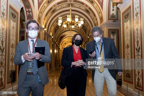 Senator Amy Klobuchar, a Democrat from Minnesota, center, wears a protective mask while departing the U.S. Capitol in Washington, D.C., U.S., on...