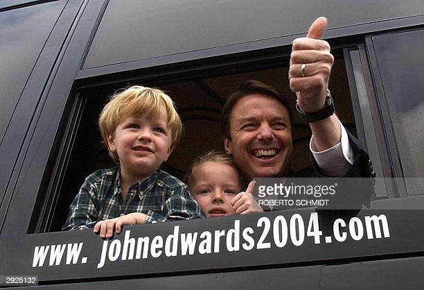 Senator and democratic presidential hopeful John Edwards makes the thumbsup sign from a window of his campaign bus with son Jack and daughter Emma...