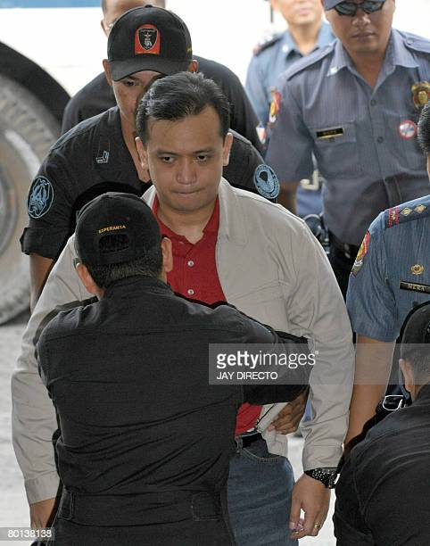 Senator and exnavy lieutenant Antonio Trillanes handcuffed to a guard is searched as he arrives for a court hearing in the financial district Makati...