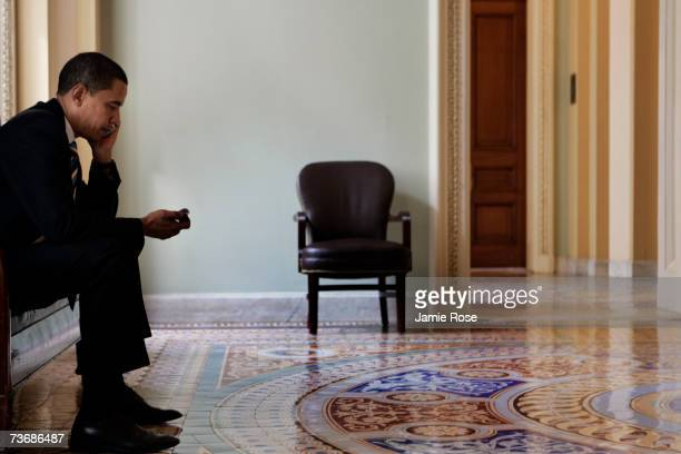 Senator Barack Obama speaks on his phone in the hallways outside of the Senate Chamber on March 23 2007 in Washington DC Lawmakers in Congress...