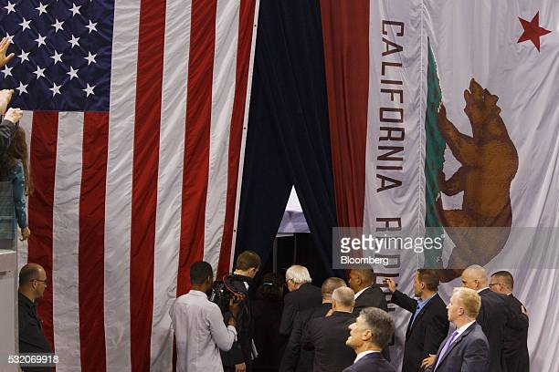 Senator Bernie Sanders an independent from Vermont and 2016 Democratic presidential candidate center right walks between an American flag and a...