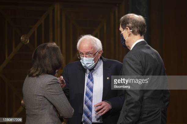 Senator Bernie Sanders, an independent from Vermont, center, wears a protective mask while talking to Senator Maria Cantwell, a Democrat from...