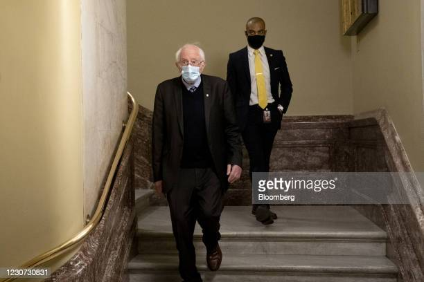 Senator Bernie Sanders, an Independent from Vermont, left, wears a protective mask while departing the U.S. Capitol in Washington, D.C., U.S., on...