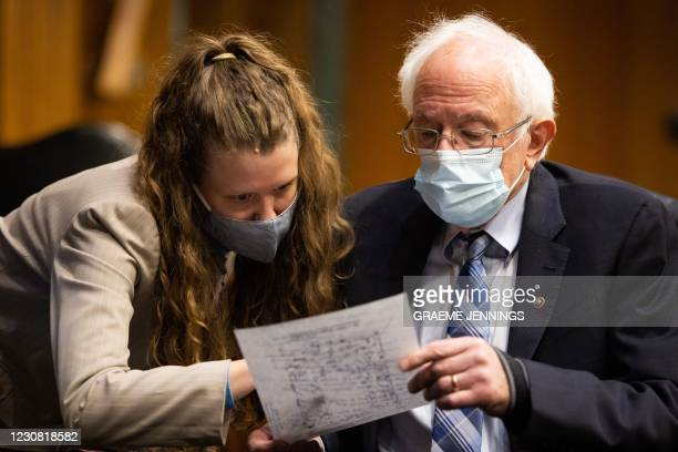Senator Bernie Sanders, I-VT, confers with a Congressional staff member during a hearing to examine the nomination of former Michigan Governor...