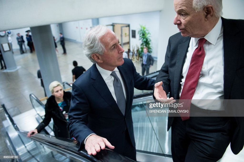 Senator Bob Corker(L) R-TN and Senator Benjamin L. Cardin (D-MD) talk while walking to a vote as lawmakers continue to work for tax reform legislation on Capitol Hill December 19, 2017 in Washington, DC. / AFP PHOTO / Brendan Smialowski