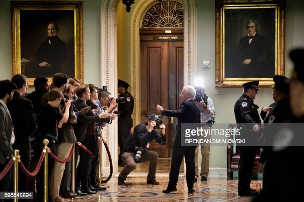 TOPSHOT Senator Bob Corker speaks with reporters while walking to a luncheon with Senate Republicans as lawmakers continue to work for tax reform...