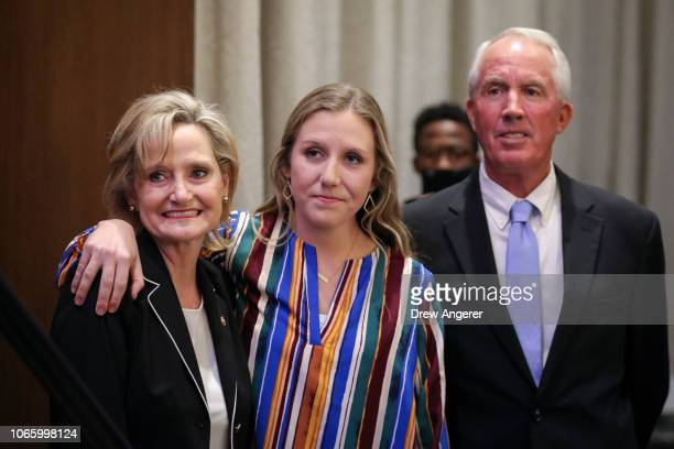 US Senator Cindy HydeSmith her daughter AnnaMichael Smith and husband Michael Smith wait to take the stage during an election night event at The...