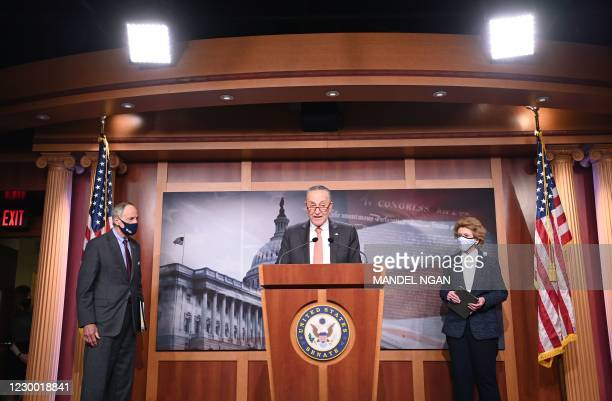 Senator Debbie Stabenow and Senator Tom Carper looks on as Senate Minority Leader Chuck Schumer speaks during a press conference at the US Capitol in...