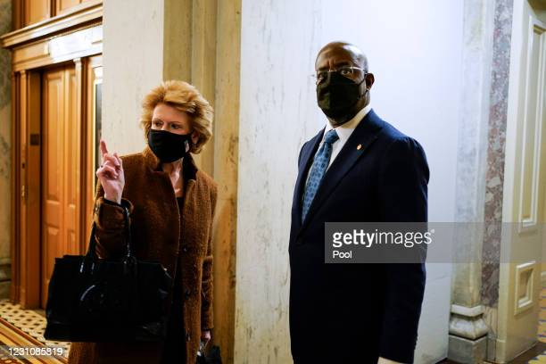 Senator Debbie Stabenow gives directions to freshman Senator Raphael Warnock as they arrive prior to the start of opening arguments on the second day...