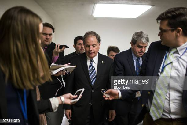 Senator Doug Jones a Democrat from Alabama center speaks to members of the media in the basement of the US Capitol in Washington DC US on Friday Jan...