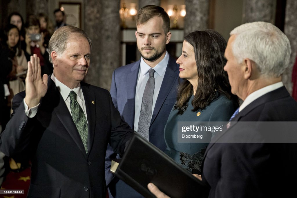 Senator Doug Jones, a Democrat from Alabama, left, is sworn-in by U.S. Vice President Mike Pence, right, during a mock swear-in ceremony with wife Louise Jones and son Carson, center, in the Old Senate Chamber of the U.S. Capitol in Washington, D.C, U.S., on Wednesday, Jan. 3, 2018. Jones won a special election over Roy Moore to fill out the rest of the unexpired term of Attorney General Jeff Sessions. Photographer: Andrew Harrer/Bloomberg via Getty Images
