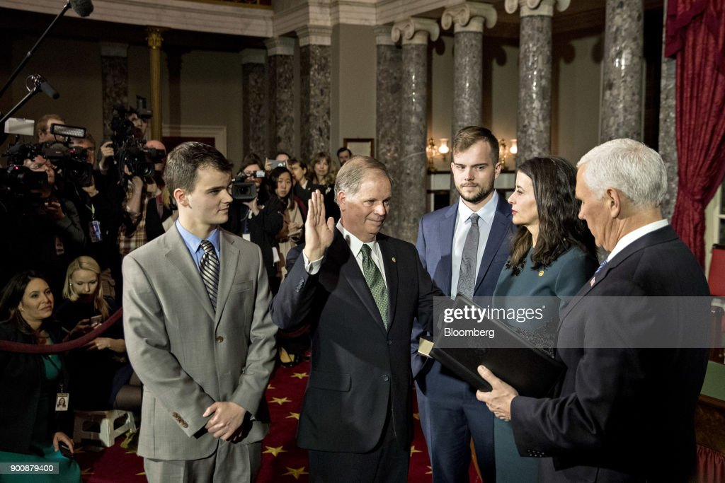Senator Doug Jones, a Democrat from Alabama, second left, is sworn-in by U.S. Vice President Mike Pence, right, during a mock swear-in ceremony with wife Louise Jones and sons Carson, center, and Christopher in the Old Senate Chamber of the U.S. Capitol in Washington, D.C, U.S., on Wednesday, Jan. 3, 2018. Jones won a special election over Roy Moore to fill out the rest of the unexpired term of Attorney General Jeff Sessions. Photographer: Andrew Harrer/Bloomberg via Getty Images
