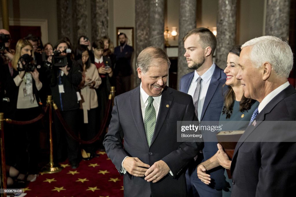 Senator Doug Jones, a Democrat from Alabama, smiles after being sworn-in by U.S. Vice President Mike Pence, right, during a mock swear-in ceremony in the Old Senate Chamber of the U.S. Capitol in Washington, D.C, U.S., on Wednesday, Jan. 3, 2018. Jones won a special election over Roy Moore to fill out the rest of the unexpired term of Attorney General Jeff Sessions. Photographer: Andrew Harrer/Bloomberg via Getty Images