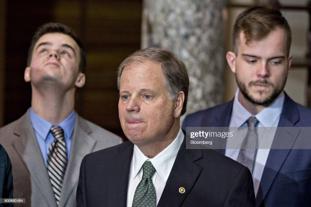 Senator Doug Jones, a Democrat from Alabama, stands next to his sons Carson, right, and Christopher after being sworn-in by U.S. Vice President Mike Pence, not pictured, during a mock swear-in ceremony in the Old Senate Chamber of the U.S. Capitol in Washington, D.C, U.S., on Wednesday, Jan. 3, 2018. Jones won a special election over Roy Moore to fill out the rest of the unexpired term of Attorney General Jeff Sessions. Photographer: Andrew Harrer/Bloomberg via Getty Images