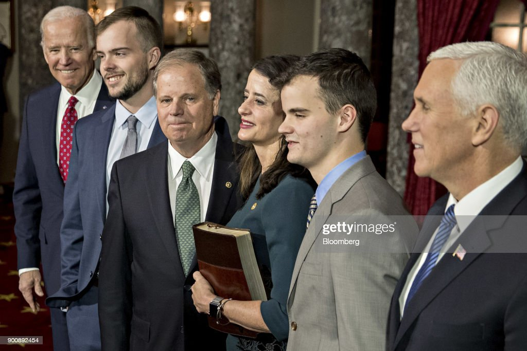 Senator Doug Jones, a Democrat from Alabama, third left, stands for a photograph after being sworn-in by U.S. Vice President Mike Pence, right, during a mock swear-in ceremony in the Old Senate Chamber of the U.S. Capitol in Washington, D.C, U.S., on Wednesday, Jan. 3, 2018. Jones won a special election over Roy Moore to fill out the rest of the unexpired term of Attorney General Jeff Sessions. Photographer: Andrew Harrer/Bloomberg via Getty Images