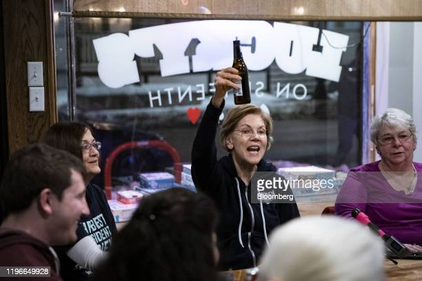 Senator Elizabeth Warren, a Democrat from Massachusetts and 2020 presidential candidate, center, offers a toast with a bottle of beer during a...
