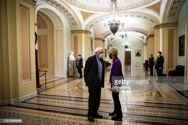 Senator Elizabeth Warren, a Democrat from Massachusetts, and Senator Bernie Sanders, an Independent from Vermont, left, wear protective masks while...
