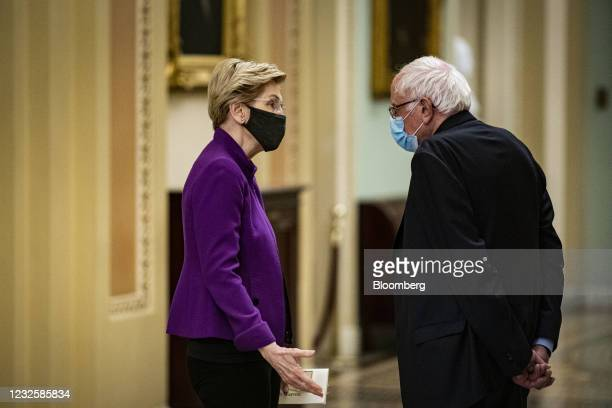 Senator Elizabeth Warren, a Democrat from Massachusetts, and Senator Bernie Sanders, an Independent from Vermont, right, wear protective masks while...