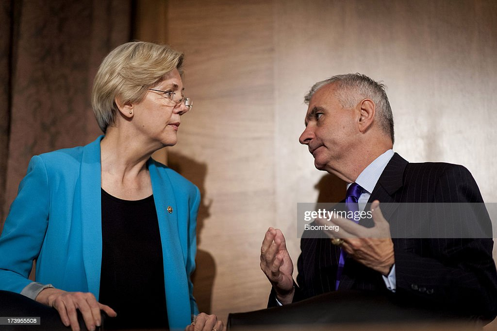 Senator Elizabeth Warren, a Democrat from Massachusetts, left, and Senator Jack Reed, a Democrat from Rhode Island, speak before the start of the Senate Banking, Housing, and Urban Affairs Committee hearing with Ben S. Bernanke, chairman of the U.S. Federal Reserve, not seen, in Washington, D.C., U.S., on Thursday, July 18, 2013. Bernanke said one reason for the recent rise in long-term interest rates is the unwinding of leveraged and 'excessively risky' investing. Photographer: Pete Marovich/Bloomberg via Getty Images