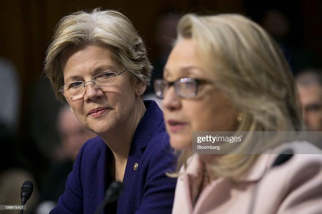 Senator Elizabeth Warren, a Democrat from Massachusetts, left, looks on as U.S. Secretary of State Hillary Clinton speaks during a Senate Foreign Relations Committee nomination hearing in Washington, D.C., U.S., on Thursday, Jan. 24, 2013. Senator John Kerry stressed the need to prevent Iran from acquiring nuclear weapons. He described the 'immediate, dangerous challenges' facing the nation as he seeks confirmation to become secretary of state. Photographer: Andrew Harrer/Bloomberg via Getty Images