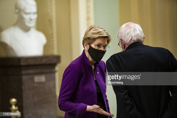 Senator Elizabeth Warren, a Democrat from Massachusetts, wears a protective mask while speaking to Senator Bernie Sanders, an Independent from...