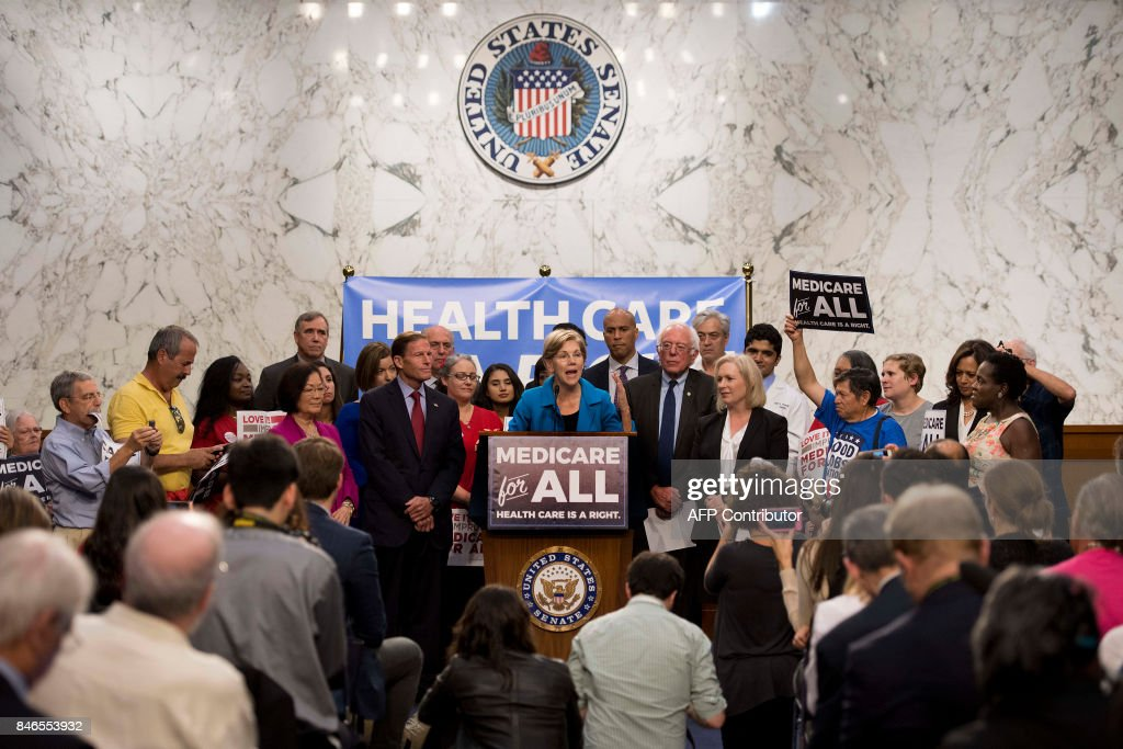 US Senator Elizabeth Warren (C), Democrat from Massachusetts, speaks with US Senator Bernie Sanders (standing next to her-R), Independent from Vermont, as they discusses Medicare for All legislation on Capitol Hill in Washington, DC, on September 13, 2017. The former US presidential hopeful introduced a plan for government-sponsored universal health care, a notion long shunned in America that has newly gained traction among rising-star Democrats. /