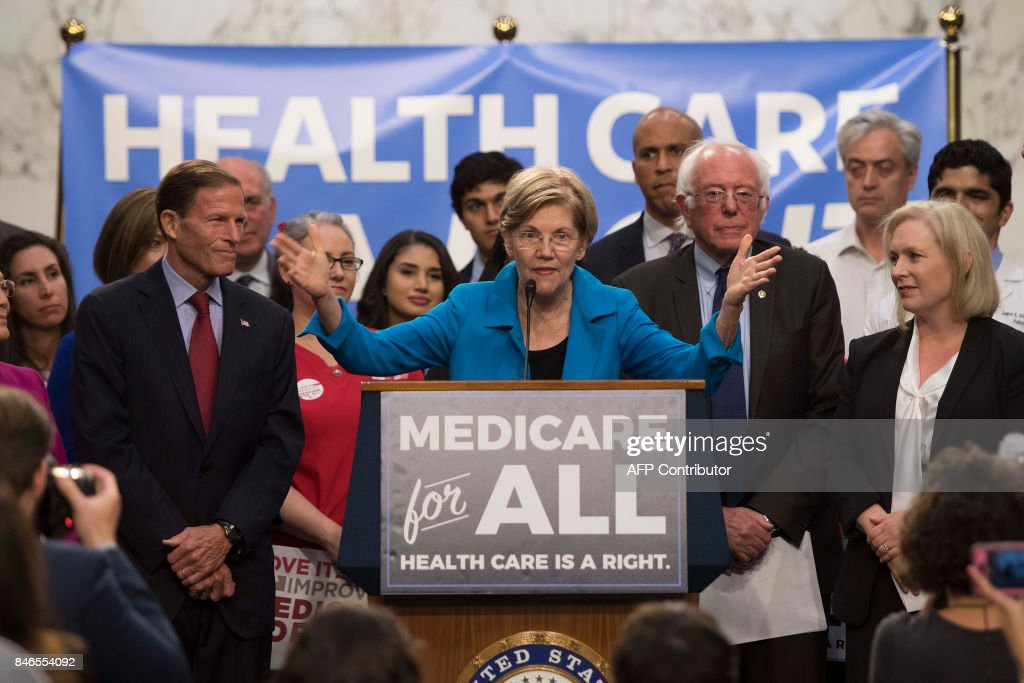 US Senator Elizabeth Warren (C), Democrat from Massachusetts, speaks with US Senator Bernie Sanders (2nd R), Independent from Vermont, as they discusses Medicare for All legislation on Capitol Hill in Washington, DC, on September 13, 2017. The former US presidential hopeful introduced a plan for government-sponsored universal health care, a notion long shunned in America that has newly gained traction among rising-star Democrats. /