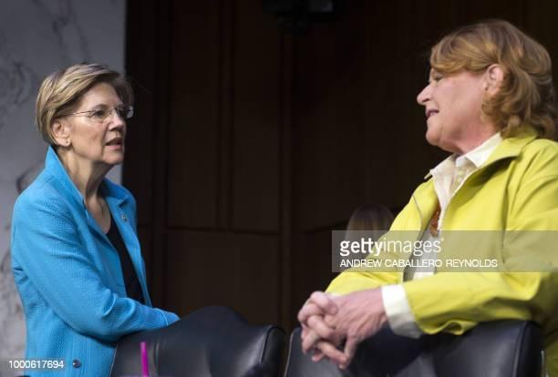 Senator Elizabeth Warren DMA speaks with Senator Heidi Heitkamp before a Senate Banking Housing and Urban Affairs Committee July 17 2018 on Capitol...