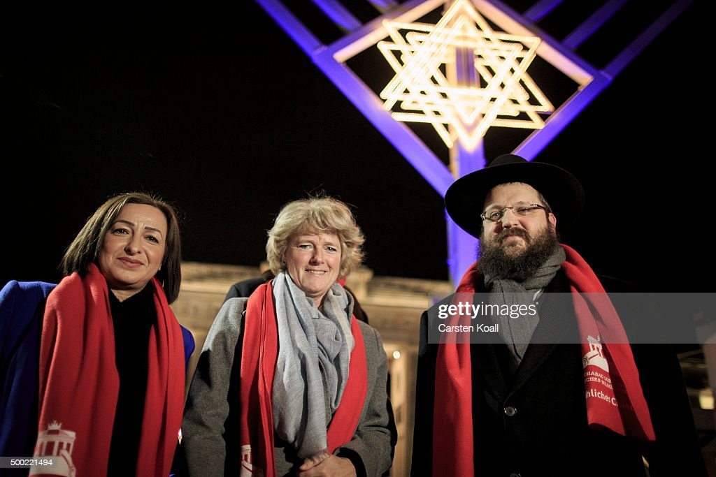 Senator for Labour, Integration and Women Dilek Kotal (L), State Minister Monika Gruetters (C) and Rabbi Yehuda Teichtal (R) attend the ceremony of the Hanukkah menorah lighting at a public Menorah ceremony near the Brandenburg Gate on December 6, 2015 in Berlin, Germany. The annual events are part of a worldwide Hanukkah campaign set into motion by the Lubavitcher Rebbe Rabbi Menachem M. Schneerson, of righteous memory.