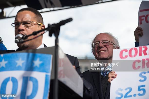 US Senator from Vermont Bernie Sanders listens to US Representative from Minnesota Keith Ellison speaking at a rally of striking federal contract...