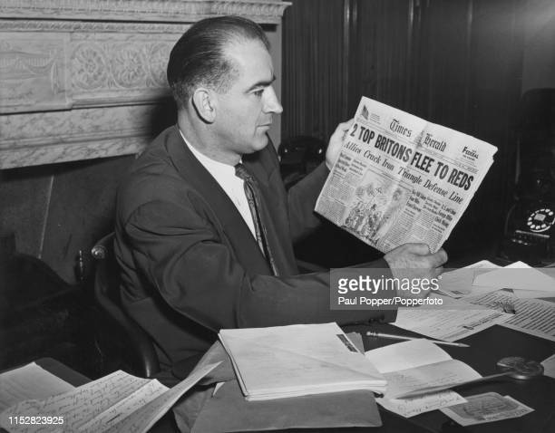 Senator from Wisconsin, Joseph McCarthy holding a copy of the Washington Times-Herald newspaper with a headline referring to the defection of British...