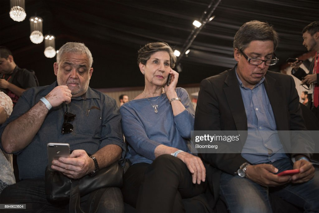 Senator Isabel Allende, daughter of late Chilean president Salvador Allende, center, speaks on a mobile device as exit poll results are announced at the New Majority coalition party headquarters after the second round presidential general elections in Santiago, Chile, on Sunday, Dec. 17, 2017. BillionaireSebastian Pineraswept to victory in the run-off of Chile's presidential election, winning by a wider than expected margin, after pledging to reverse four years of sluggish economic growth. Photographer: Tamara Merino/Bloomberg via Getty Images