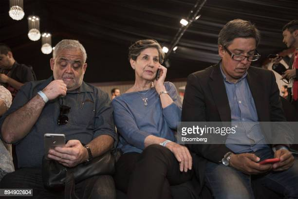 Senator Isabel Allende daughter of late Chilean president Salvador Allende center speaks on a mobile device as exit poll results are announced at the...