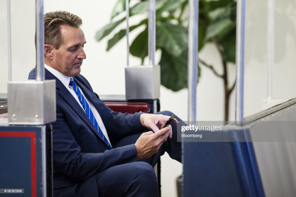Senator Jeff Flake, a Republican from Arizona, checks a mobile device while sitting on the Senate Subway in the basement of the U.S. Capitol in Washington, D.C., U.S., on Wednesday, Feb. 14, 2018. A bipartisan Senate group tentatively agreed on a trimmed-down immigration proposal Wednesday that would allow citizenship for young undocumented immigrants and provide $25 billion for a border wall without meeting White House demands for cuts in family migration and eliminating a visa lottery. Photographer: Zach Gibson/Bloomberg via Getty Images