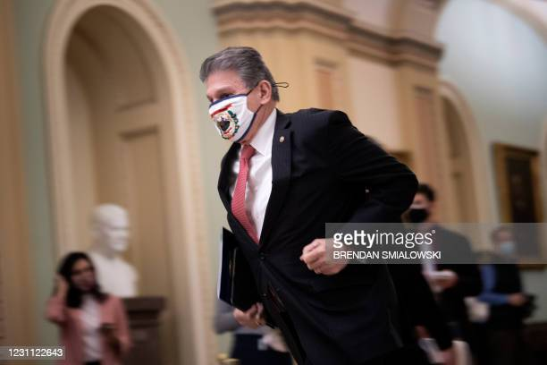 Senator Joe Manchin III runs to the Senate floor for the fourth day of former US President Donald Trump's impeachment trial before the Senate on...
