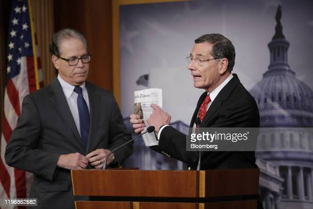 Senator John Barrasso a Republican from Wyoming right speaks while holding up a copy of the New York Times newspaper during a news conference at the...