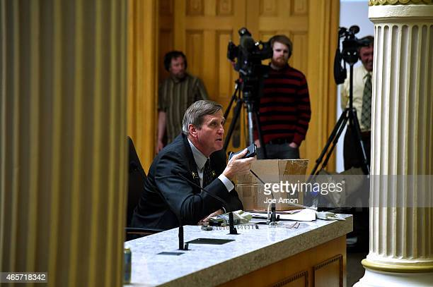 Senator John Cooke of Greeley hold a magazine as he speaks to the Senate Judiciary Committee during a hearing for Senate Bill 175 by Republican...