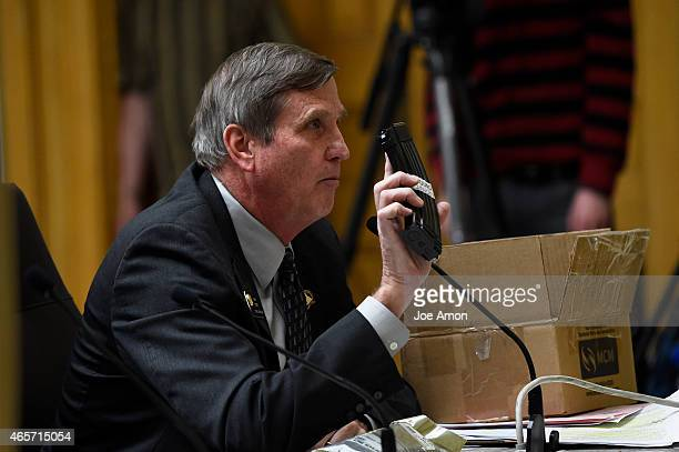 Senator John Cooke of Greeley hold a magazine that can be modified to hold 30 rounds as he speaks to the Senate Judiciary Committee during a hearing...
