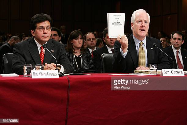 S Senator John Cornyn holds up a copy of the Commentary of Geneva Convention as White House Counsel Alberto R Gonzales looks on during Gonzales'...