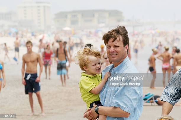 Senator John Edwards holds his son Jack during his Fifth Annual Beach Walk July 4 2003 at Wrightsville Beach NC As Edwards a candidate for democratic...
