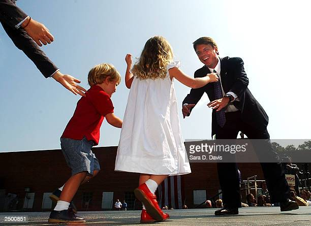 S Senator John Edwards reaches for his children Jack and Emma Claire at the formal announcement of his candidacy for the presidency at the Old...
