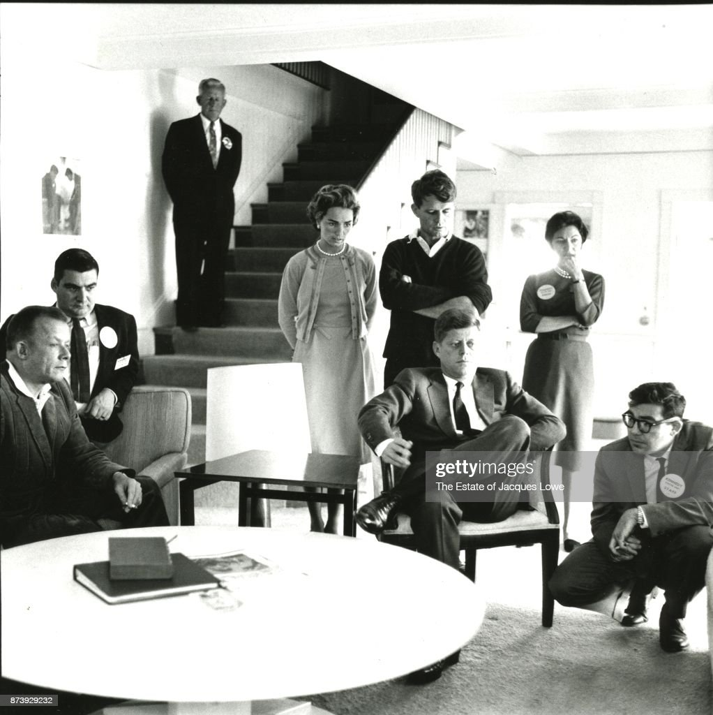 Senator (and soon-to-be US President) John F Kennedy (1917 - 1963) (seated center) and family members, friends, and aides watch returns in the 1960 Presidential Election on television, Hyannis Port, Massachusetts, November 1960. Pictured are, fore from left, Bill Walton, Pierre Salinger (1925 - 2004), Ethel Skakel Kennedy, Robert F Kennedy (1925 - 1968) (standing, arms folded), JFK, RFK's secretary Angie Novello, and William F Haddad.