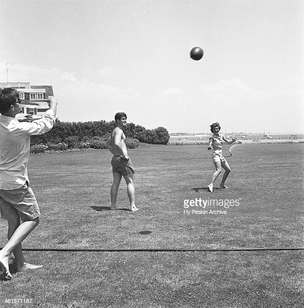Senator John F Kennedy and fiance Jacqueline Bouvier play footballl with Edward Kennedy while on vacation at the Kennedy compound in June 1953 in...
