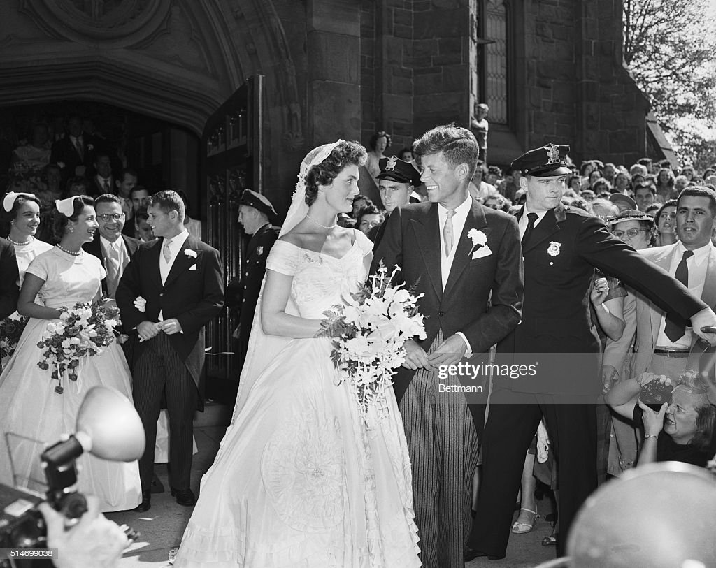 Senator John F. Kennedy and his bride, the former Jacqueline Lee Bouvier, leave a Newport, Rhode Island, church following their wedding ceremony. An estimated one thousand people waited outside the church for the newlyweds.