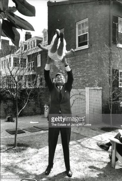 Senator John F Kennedy swings his daughter Caroline in the air in the yard of their townhouse in the Georgetown neighborhood Washington DC Spring 1959