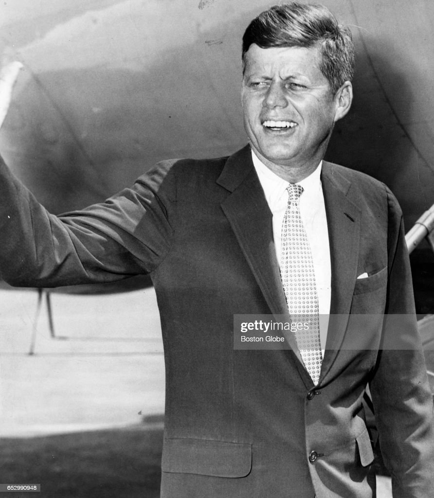 Senator John F. Kennedy waves as he leaves Logan International Airport in Boston on June 16, 1960.